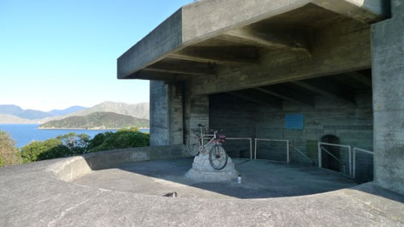 The Fort on Maud Island, a concrete structure with a bicycle in the middle and islands in the background.