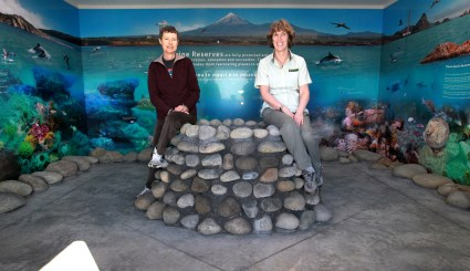 NMRS's Barbara Hammonds and DOC's Kay Davies perch on the edge of a rock pool in the centre.