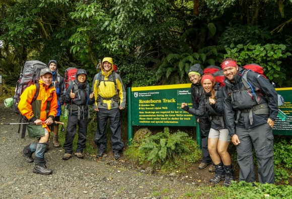 Standing beside the Routeburn Track sign on a wet day.
