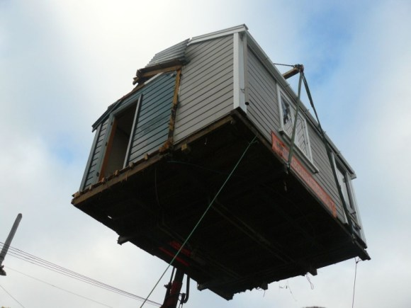 Scott's cabin is hoisted by crane on to a truck.