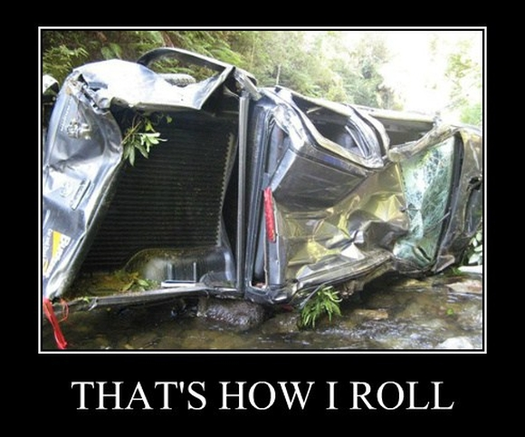 The rolled ute at the bottom of a cliff.