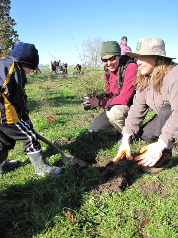 Young boy planting with a DOC ranger.