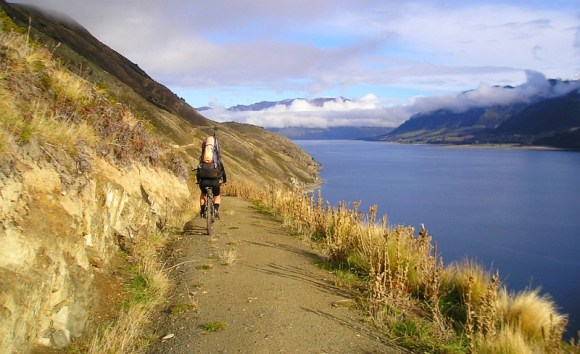 Mountain biking beside Lake Hāwea in Hāwea Conservation Park. Photographed by John Robinson.