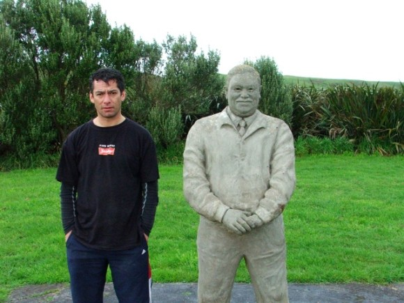 Roland standing beside the Tame Horomona-Rehe memorial statue on the Chatham Islands.