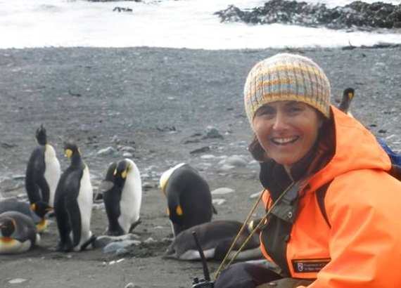 Kirsten Ralph on Macquarie island with penguins in the background.