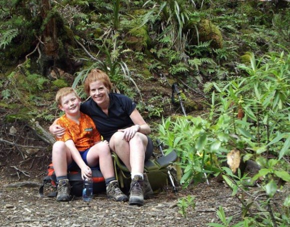 Nina and her son, Fenn, in tramping gear sitting by the track in the bush.
