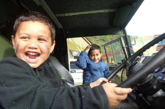 Children sitting in the Pinzgauer six-wheeler truck.