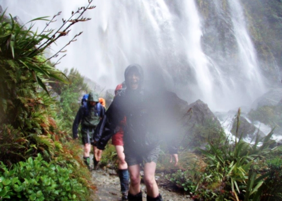 Caroline with a group on the Routeburn Track near a waterfall.