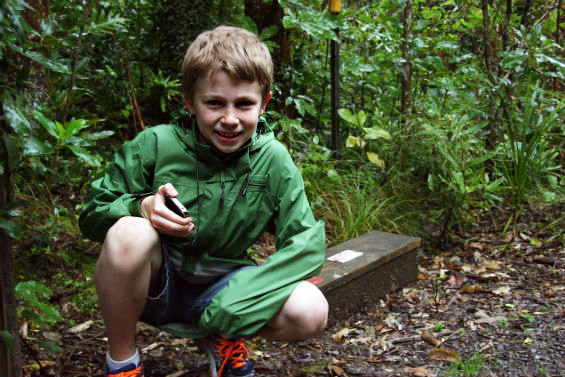 Finn with smartphone in the bush at Zealandia.