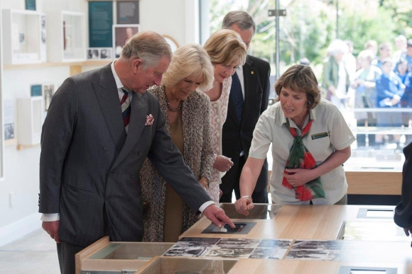 Kay Davies showing Prince Charles and Lady Camilla around the Government House Visitor Centre.
