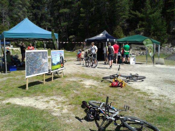 Kaiteriteri Mountain Bike Park full of people, signs, tents and bikes.