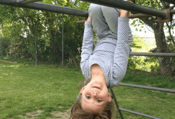 Esme hanging upside down on the monkey bars.