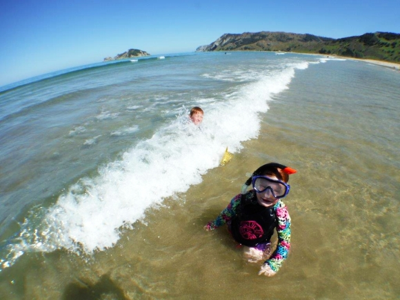 Kids swimming in the waves at Anaura Bay beach.