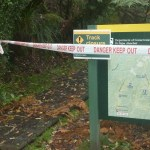 DOC sign with 'Danger Keep Out' barrier tape across it and the track that the sign marks.