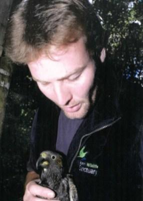 Mark Kearney holding a kākā.