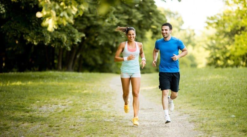 Imagem de um casal praticando a corrida num parque para cuidar da saúde