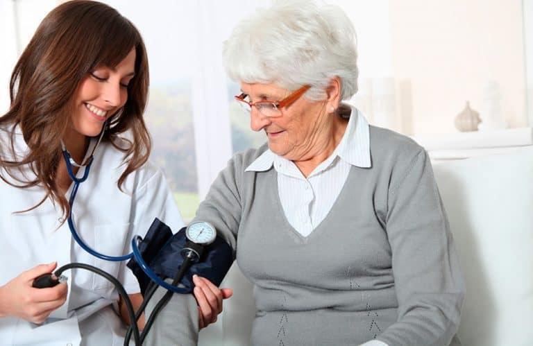 Uma médica fazendo um check up em uma senhorinha, medindo sua pressão.
