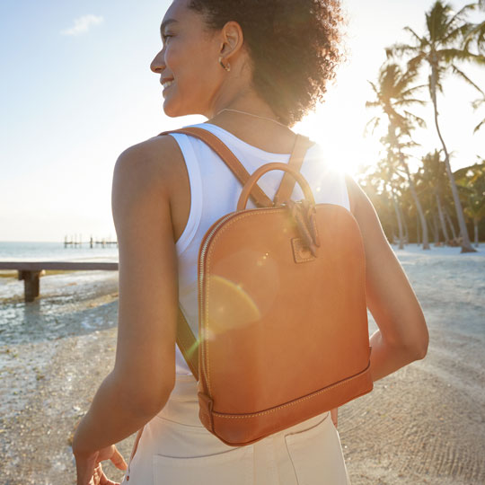 Woman wearing a Dooney & Bourke backpack, the best commuter bag, on the beach.