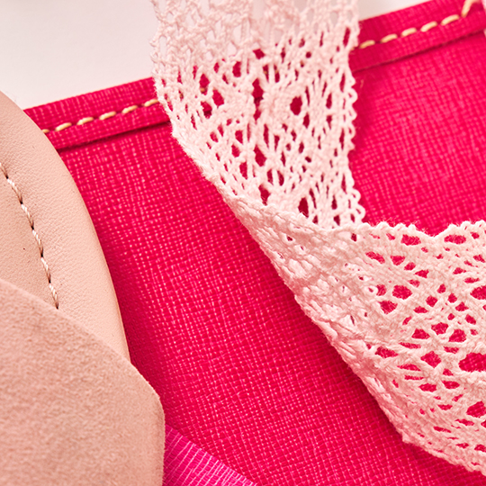 Up-close image of pink lace and pink leather.