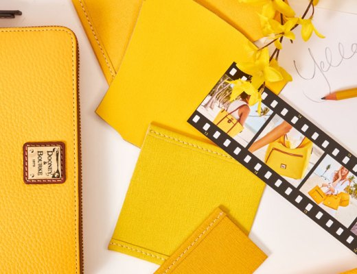 A yellow Dooney & Bourke wallet sits with leather swatches and film.