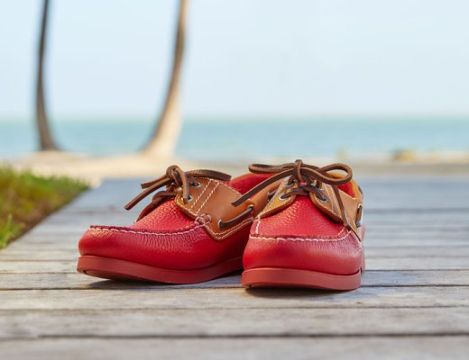 A pair of red leather boat shoes sit on a pier.