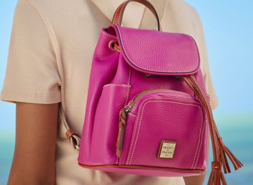 Woman wearing pink Dooney & Bourke backpack.