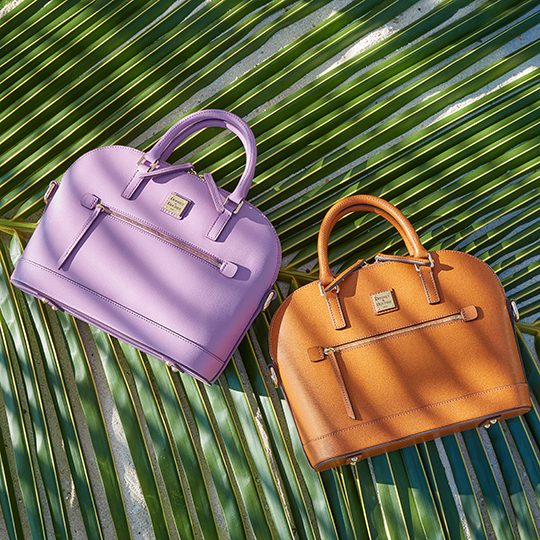 Two Dooney & Bourke Saffiano satchels on a palm frond.