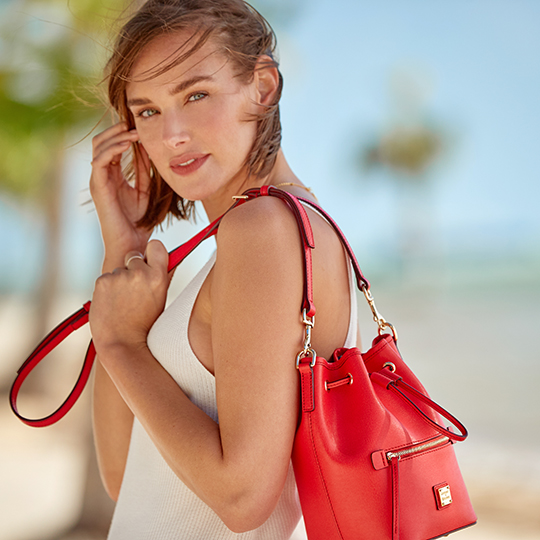 A woman wears the Saffiano Drawstring bag in tomato.