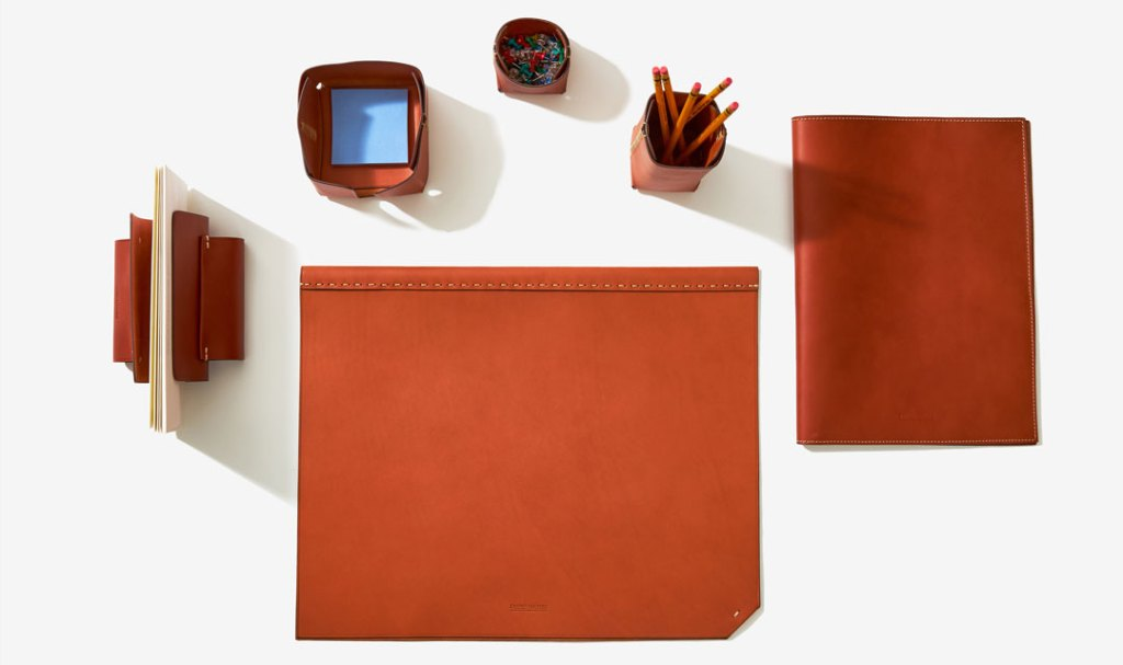 Leather desk accessories arranged next to each other, including a leather pencil holder, post-it note holder, folder, and desk pad.