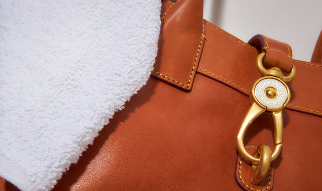 A Florentine leather handbag with a wash cloth resting on top of it.