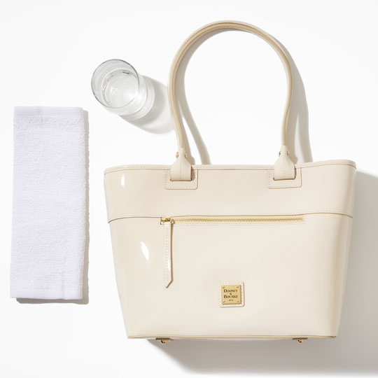 A patent leather handbag, a folded cotton cloth, and a cup of distilled water.