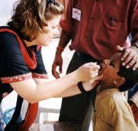 A woman administering a polio vaccine to a child's mouth.
