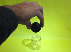 A person holding a squash ball. In the background, there is a jar. The jar and the ball appear the same width.