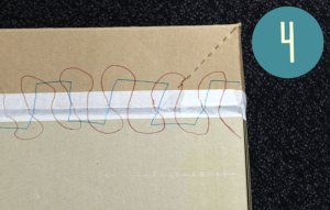 a lid is taped to a cardboard box - and there are squiggles drawn all over it