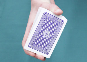 Someone is holding a deck of cards between their thumb and fingers.
