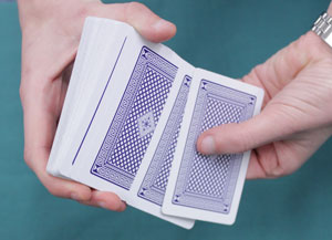 Someone has cupped their left hand around the deck of cards and is shuffling them.