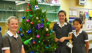Three girls from the grade 7 class from Kambala High standing next to a Christmas tree