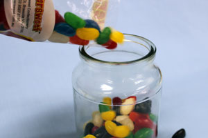 someoen is pouring jellybeans into a jar.
