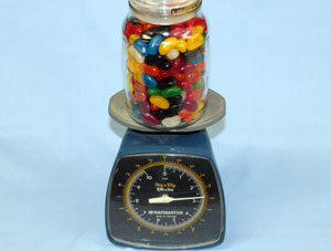 a jar of jellybeans on a set of scales.