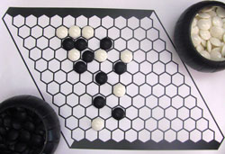 A hexagonal grid with black and white counters on it.