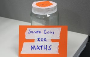 A jar with a slot in the top and a sign saying 'silver coins for maths'.