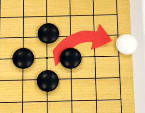 Four black stones surround the white sone's original position. The white stone is removed from the board.