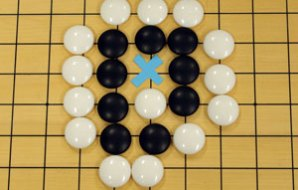 Several black stones are surounded by white stones. One space is indicated by an x.