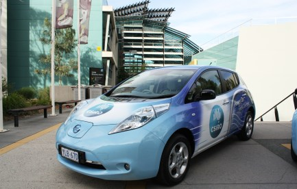 An electric car outside a big building.