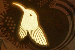 A bright bird shape on a dark background.