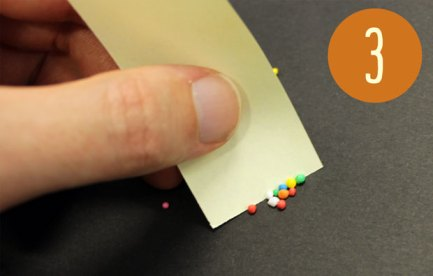 Someone separating 10 sprinkles with a piece of paper.