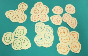 small circles of paper with the numbers 1, 2, 5, 13, 29 and 64 written on them.