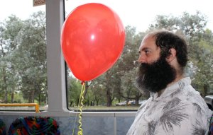 A man sitting on a bus holding a red balloon on a string.