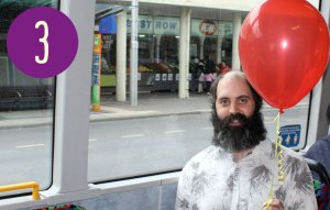 A man on a bus holding a red balloon on a string