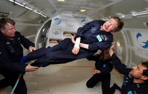 Photograph of Stephen Hawkings floating in a capsule with three people assisting him.